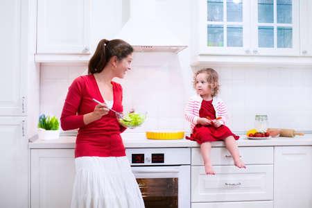 Madre e hijo hornear un pastel. Mujer joven y su hija cocinar en una cocina blanca. Niños hornear pasteles. Niños ayudando a hacer la cena. Interior moderno con electrodomésticos horno y otros. Comer Familia. Foto de archivo - 41386730
