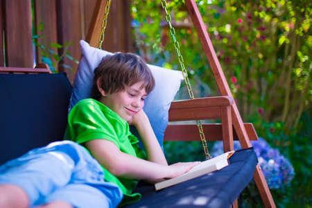 columpio: Feliz ni�o de la escuela la lectura de un libro en el patio trasero. Ni�o que se relaja en un columpio de jard�n con los libros. Los ni�os leen durante las vacaciones de verano. Ni�os estudiando. Adolescente chico haciendo la tarea al aire libre.