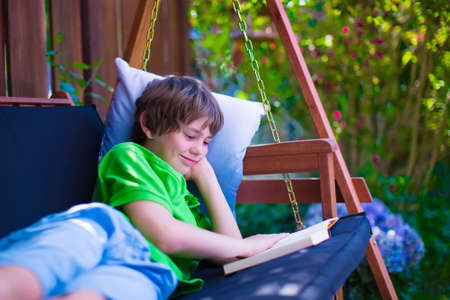 comfortable cozy: Happy school boy reading a book in the backyard. Child relaxing in a garden swing with books. Kids read during summer vacation. Children studying. Teenager kid doing homework outdoors.
