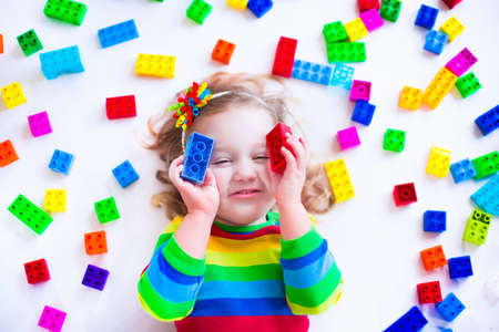カラフルなおもちゃのブロックと遊ぶ幼児子供。子供は、幼稚園や保育教育のおもちゃで遊ぶ。就学前の子供は、プラスチック ブロックの塔を建て