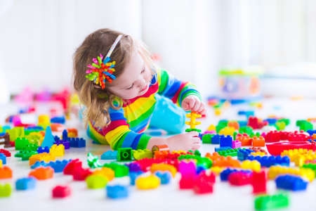 Preschooler child playing with colorful toy blocks. Kids play with educational toys at kindergarten or day care. Preschool children build tower with plastic block. Toddler kid in nursery. Stock Photo