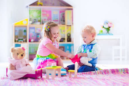 plush toys: Kids playing with doll house and stuffed animal toys. Children sit on a pink rug in a play room at home or kindergarten. Toddler kid and baby with plush toy and dolls. Birthday party for little child. Stock Photo