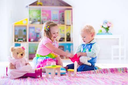 niñas jugando: Niños jugando con casa de muñecas y juguetes de peluche. Los niños se sientan en una manta de color rosa en una sala de juegos en la casa o el jardín de infantes. Niño niño y el bebé con el juguete de felpa y muñecas. Fiesta de cumpleaños de niño pequeño.