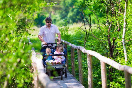 Young active father with kids in double stroller in a park. Dad with twin pram walking in the forest. Parent with twins son and daughter hiking in the woods. Outdoor fun for family with children. Zdjęcie Seryjne