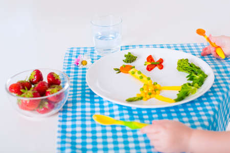 eating right: Healthy vegetarian lunch for little kids. Kid meal. Vegetable and fruit served as animals corn broccoli carrot strawberry helping child to learn eating right and clean children hands with spoon Stock Photo