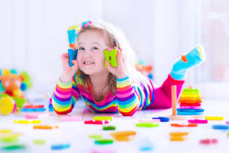 Preschooler child playing with colorful toy blocks. Kids play with educational wooden toys at kindergarten or day care. Preschool children build tower with wood block. Toddler kid in nursery. Banco de Imagens