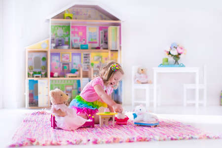 Little girl playing. Kids with doll house and stuffed animal toys. Children sit on a pink rug in a play room at home or kindergarten. Toddler kid with plush toy and dolls. Birthday party for little child. Stock Photo