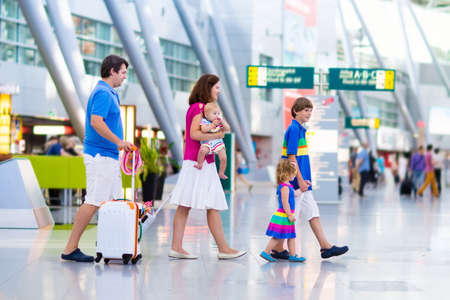depart: Family traveling with kids. Parents with children at international airport with luggage. Mother and father hold baby toddler girl and boy flying by airplane. Travel with child for summer vacation.