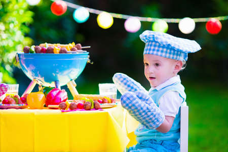corn meal: Children grilling meat. Family camping and enjoying BBQ. Little boy at barbecue preparing steaks kebab and corn. Kids eating grill and healthy vegetable meal outdoors. Garden party for toddler child