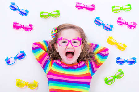 optician: Child wearing eye glasses. Eye wear for kids. Little girl choosing spectacles. Lens and colorful frame choice for children. Vision and sight control at optician shop. Smart preschooler with eyeglasses Stock Photo