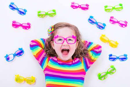 Niño que lleva gafas. Gafas para los niños. Niña elegir las gafas. Lente y la elección marco colorido para los niños. Visión y control de la vista en la tienda de óptica. Preescolar inteligente con gafas