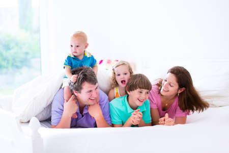 large family: Family with three kids in bedroom