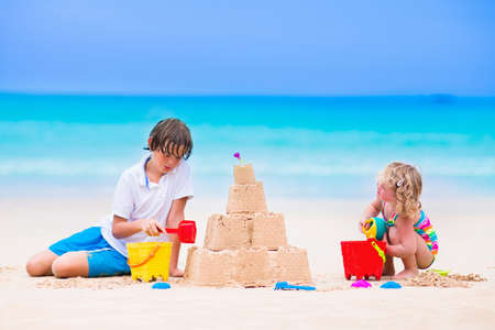 playing in the sea: Kids playing on a beach. Two children build a sand castle at the sea shore. Family vacation on a tropical island. Boy and girl digging with toy spade and kid spade. Traveling with young child.