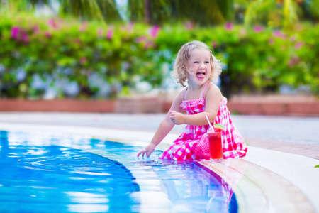 fiesta familiar: Hermoso ni�o ni�a linda con el pelo rizado con un vestido rojo de verano que se sienta en una piscina bebiendo jugo de sand�a con fruta fresca divertirse durante las vacaciones de la familia en un resort tropical