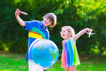 school age boy: Two happy children cute curly toddler girl and a smiling school age boy play with toy airplanes flying over the globe dreaming of traveling around the world. Kids fly and travel with airplane. Stock Photo