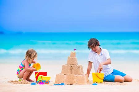 Niños jugando en una playa. Dos niños a construir un castillo de arena en la orilla del mar. Familia de vacaciones en una isla tropical. Niño y niña cavando con pala de juguete y el niño por su nombre. Viajar con niños pequeños.