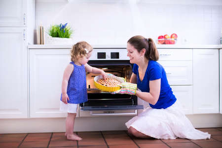 Mother and child bake a pie. Young woman and her daughter cook in a white kitchen. Kids baking pastry. Children helping to make dinner. Modern interior with oven and other appliances. Family eating.