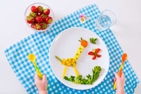 Healthy vegetarian lunch for little kids. Kid meal. Vegetable and fruit served as animals corn broccoli carrot strawberry helping child to learn eating right and clean children hands with spoon Standard-Bild