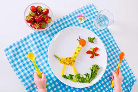 Gezonde vegetarische lunch voor kleine kinderen. Kid maaltijd. Groente en fruit diende als dieren maïs broccoli aardbei helpen kind om te leren eten van rechts en schone handen van kinderen met lepel Stockfoto