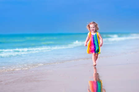 running water: Happy laughing little girl in colorful rainbow bathing suit running and playing on ocean coast in water splashes on beautiful tropical island beach with turquoise clear water having fun on vacation