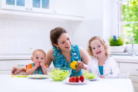 comidas: Joven madre y dos ni�os que cocinan en la cocina. Padres y ni�os cocinan la cena. Familia con el beb� y el ni�o ni�o coma en su casa. Ni�o preparar y comer el almuerzo vegetal. Preescolar nutrici�n saludable Foto de archivo