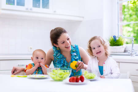 preschooler: Young mother and two children cooking in a kitchen. Parent and kids cook dinner. Family with baby and toddler kid eat at home. Child preparing and eating vegetable lunch. Preschooler healthy nutrition