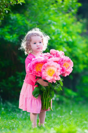 Little cute girl with peony flowers child wearing a pink dress little cute girl with peony flowers child wearing a pink dress playing in a summer mightylinksfo