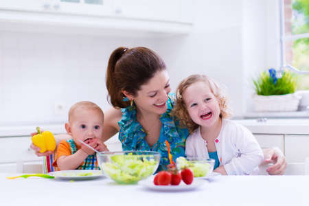 kids eating healthy: Young mother and two children cooking in a kitchen. Parent and kids cook dinner. Family with baby and toddler kid eat at home. Child preparing and eating vegetable lunch. Preschooler healthy nutrition