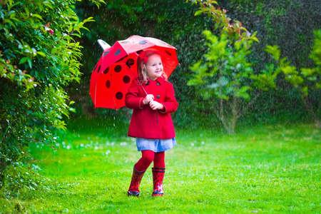 botas de lluvia: Ni�a con el paraguas rojo que juega en la lluvia. Los ni�os juegan al aire libre por el tiempo lluvioso en el oto�o. Oto�o diversi�n al aire libre para los ni�os. Chico Ni�o en impermeable y botas para caminar en el jard�n. Ducha de verano.