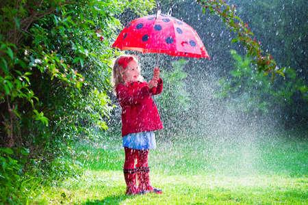 lluvia paraguas: Niña con el paraguas rojo que juega en la lluvia. Los niños juegan al aire libre por el tiempo lluvioso en el otoño. Otoño diversión al aire libre para los niños. Chico Niño en impermeable y botas para caminar en el jardín. Ducha de verano.