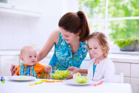 healthy nutrition: Young mother and two children cooking in a kitchen. Parent and kids cook dinner. Family with baby and toddler kid eat at home. Child preparing and eating vegetable lunch. Preschooler healthy nutrition