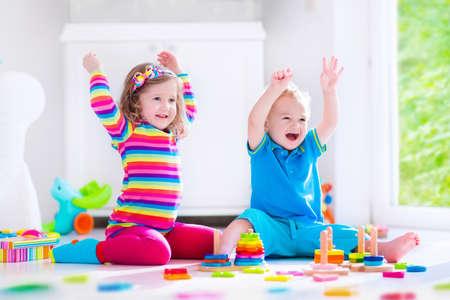 Preescolar niño jugando con bloques de juguete de colores. Los niños juegan con los juguetes de madera educativos en jardín de infantes o guardería. Los niños de preescolar construir la torre con el bloque de madera. Niño del niño en la guardería.
