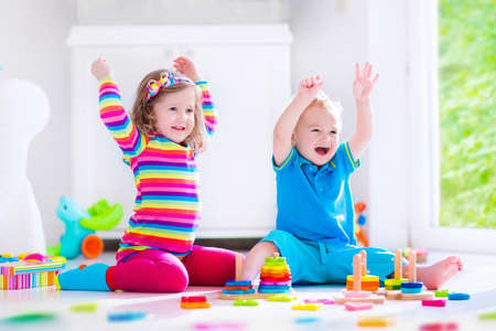 Preschooler child playing with colorful toy blocks. Kids play with educational wooden toys at kindergarten or day care. Preschool children build tower with wood block. Toddler kid in nursery. Foto de archivo