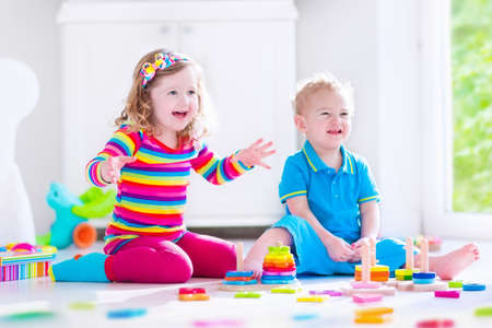 kindergarten toys: Preschooler child playing with colorful toy blocks. Kids play with educational wooden toys at kindergarten or day care. Preschool children build tower with wood block. Toddler kid in nursery. Stock Photo