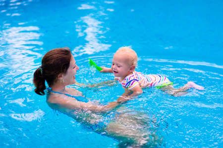 splash pool: Mother and baby in swimming pool. Parent and child swim in a tropical resort. Summer outdoor activity for family with kids. Vacation and traveling with young children. Inflatable toys for water fun.