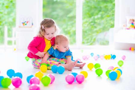 juguetes: Los niños juegan con los juguetes de bolas de colores. Los niños juegan con pelotas de juguete. Niño niño y el bebé al cuidado en el hogar o días. Niño en preescolar o jardín de infantes. Guardería blanca con ventana grande para niño y niña
