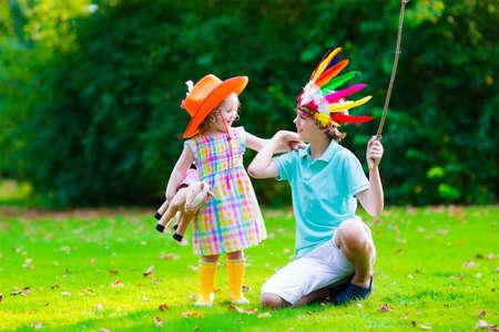 Niños en vaquero y vaquera trajes jugando al aire libre. Los niños juegan con el caballo de juguete. Muchacho en sombrero de nativos americanos en la fiesta de Acción de Gracias. Niño del niño y el niño de la escuela durante el truco o tratar en Halloween. Foto de archivo