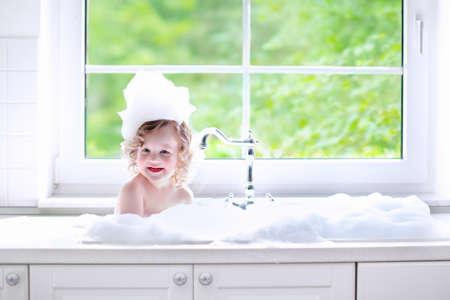 cuarto de baño: Niño que toma el baño. Pequeño bebé en un cabello lavado fregadero de la cocina con champú y jabón. Niños jugando con salpicaduras de espuma y agua. Cuarto de baño blanco con ventana. Chico limpio después de la ducha. Higiene infantil.