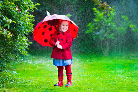the weather: Niña con el paraguas rojo que juega en la lluvia. Los niños juegan al aire libre por el tiempo lluvioso en el otoño. Otoño diversión al aire libre para los niños. Chico Niño en impermeable y botas para caminar en el jardín. Ducha de verano.