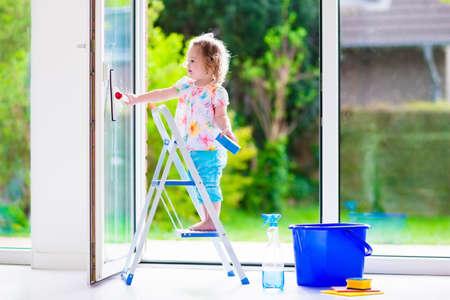 창을 세척 어린 소녀. 아이들은 집을 청소. 아이들은 집에 도움이됩니다. 사다리에 서있는 창문과 문을 청소 유아 아이. 집안일 유지 스폰지와 비누 병
