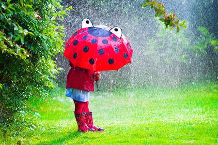 botas: Niña con el paraguas rojo que juega en la lluvia. Los niños juegan al aire libre por el tiempo lluvioso en el otoño. Otoño diversión al aire libre para los niños. Chico Niño en impermeable y botas para caminar en el jardín. Ducha de verano.