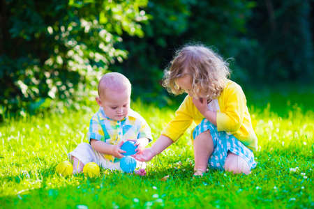 day care: Children playing in the garden. Toddler kid and little baby play outdoors in summer. Girl and boy with toy balls at day care or kindergarten. Child with colorful ball. Outdoor toys for kids.