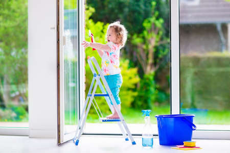 limpieza  del hogar: Niña lavar una ventana. Niños limpiar la casa. Los niños ayudan en casa. Chico Niño ventanas y puertas de pie en una escalera de la limpieza. Niño ayudando con las tareas del hogar celebración esponja y botella de jabón.