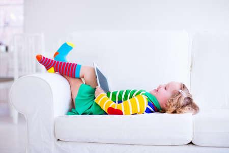 Petite fille tenant tablet pc détente sur un canapé blanc. Les enfants utilisant un ordinateur à la maison ou préscolaire. Les enfants qui apprennent avec des appareils numériques. Enfant jouant jeu en ligne. enfant en bas âge et gadget moderne. Banque d'images - 41733562
