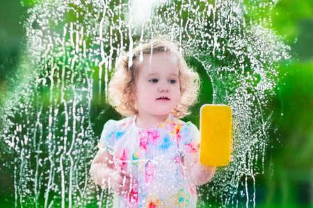Dzieci: Dziewczynka mycie okien. Dzieci posprzątać dom. Dzieci pomagają w domu. Maluch dzieciak czyszczenia okien i drzwi, stojąc na drabinie. Dziecko pomaga w pracach domowych holdingowej gąbką i butelki z mydłem.