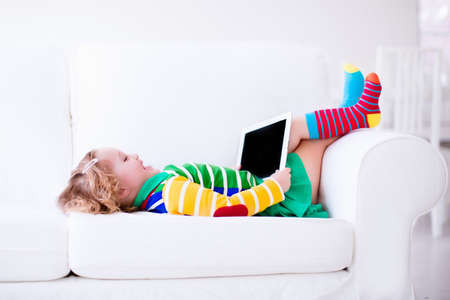 digital tablet: Little girl holding tablet pc relaxing on a white couch. Kids using computer at home or preschool. Children learning with digital devices. Child playing online game. Toddler kid and modern gadget.