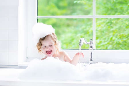Child taking bath. Little baby in a bath tub washing hair with shampoo and soap. Kids playing with foam and water splashes. White bathroom with window. Clean kid after shower. Children hygiene. Zdjęcie Seryjne