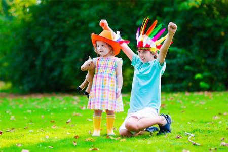 Kids in Cowboy und Cowgirl Kostüme Spielen im Freien. Kinder spielen mit Spielzeugpferd. Boy in Native American Hut auf Thanksgiving Partei. Kleinkind Kind und Schulkind während trick or treat Halloween an.