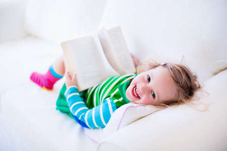 Little girl reading a book relaxing on a white couch. Kids read books at home or preschool. Children learning and doing homework after school. Child playing. Toddler kid in colorful dress on a sofa.