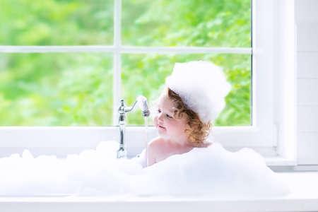 Niño que toma el baño. Pequeño bebé en un cabello lavado tina de baño con champú y jabón. Niños jugando con salpicaduras de espuma y agua. Cuarto de baño blanco con ventana. Chico limpio después de la ducha. Higiene infantil.